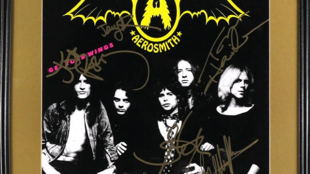 A fully band signed Aerosmith 'Get Your Wings' LP cover from 1974, featuring the autographs of Steven Tyler, Joe Perry, Tom Hamilton, Joey Kramer and Brad Whitford. All signatures are nicely done with a gold marker. The album cover is matted and housed in a 16 1/2 x 16 1/2 inch frame. Excellent condition. From the the private collection of David Frangioni.