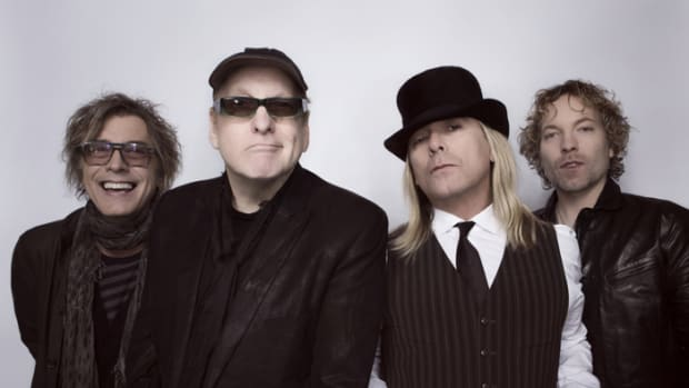 "CURRENT TRICK (L-R): Tom Petersson, Rick Nielsen, Robin Zander, Daxx Nielsen and their newest album, ""We're All Alright!"" Photo by David McClister."