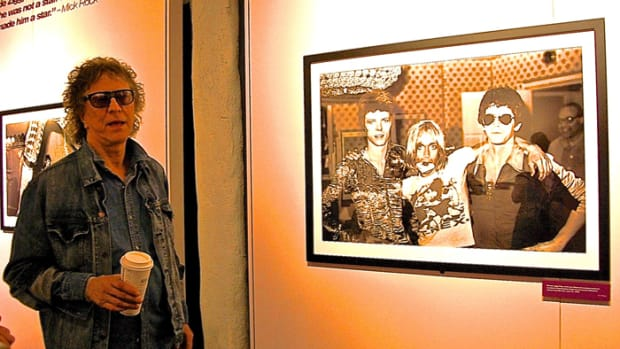 Mick Rock standing next to his famous Bowie/Pop/Reed photo