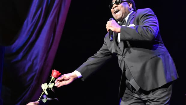 Al Green passes a rose to a female fan early in his May 5 show at Radio City Music Hall in New York. (Photo by Chris M. Junior)