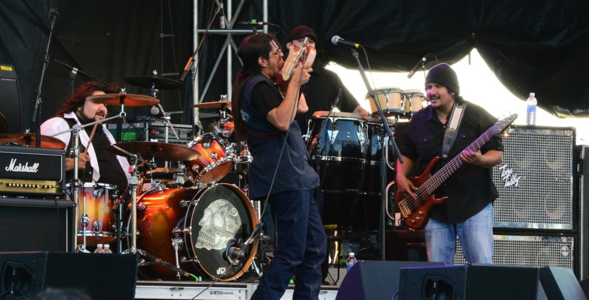 Los Lonely Boys guitarist Henry Garza takes a Jimi Hendrix-type approach to his instrument while brothers and bandmates Ringo (left) and Jojo watch. (Photo by Chris M. Junior)