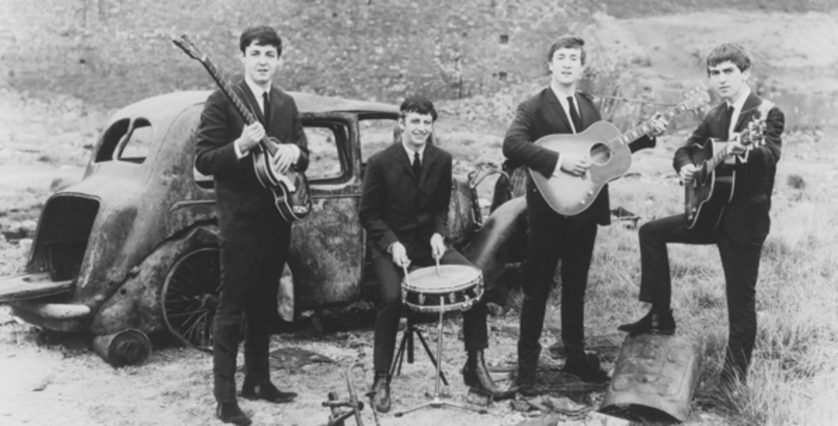 A very young Fab Four get down and dirty at a junkyard for this early press photograph . Photo courtesy of Parlophone/Apple Corps Ltd.