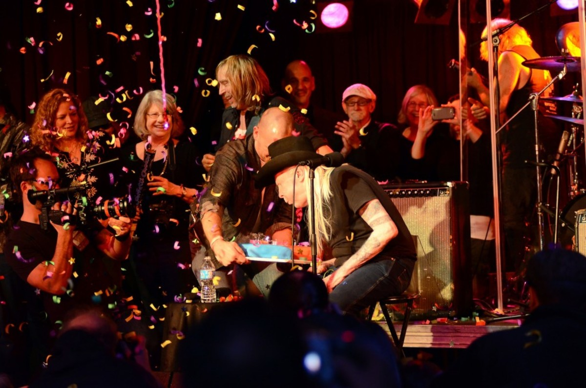 Johnny Winter blows out the candles on his birthday cake. (Photo by Chris M. Junior)