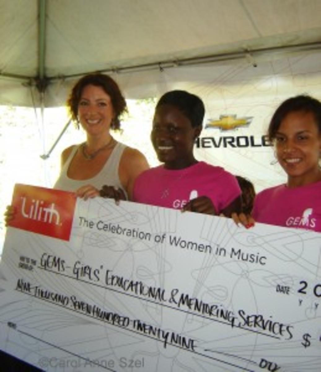 Sarah giving check to charity