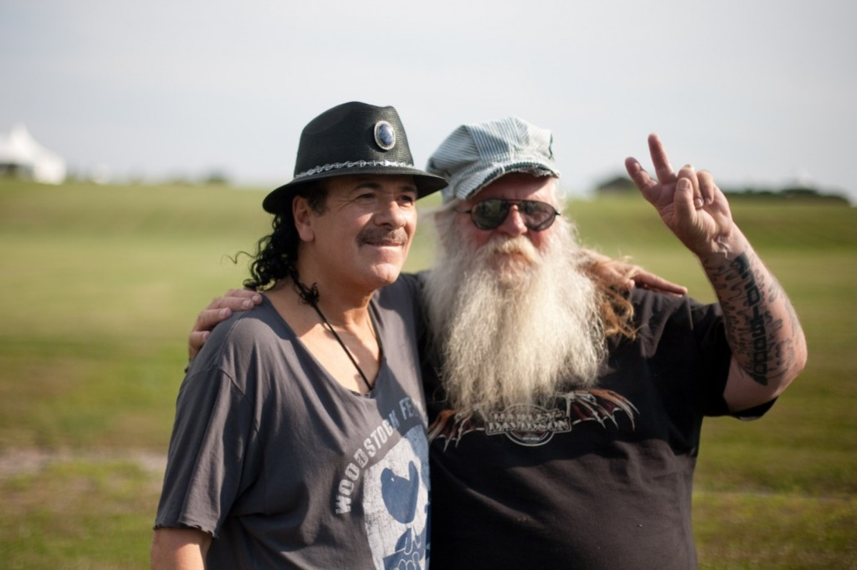Before his sold out show Carlos Santana poses at the site of the 1969 Woodstock festival at Bethel Woods Center for the Arts, with Duke Devlin Site Intrepretor at Bethel Woods. Photo courtesy of Michael Bloom for Bethel Woods.