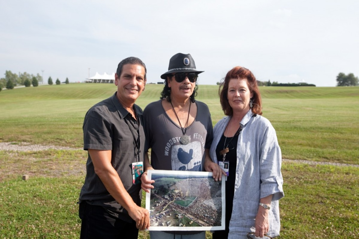 Before his sold out show Carlos Santana poses at the site of the 1969 Woodstock festival at Bethel Woods Center for the Arts, with Jason Stone Vice President-General Manager of Live Nation and Darlene Fedun COO of Bethel Woods. Photo courtesy of Michael Bloom for Bethel Woods.