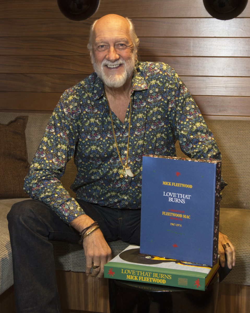 "Mick Fleetwood posing with his latest book, ""Love That Burns."" Photo by Chris M. Junior"
