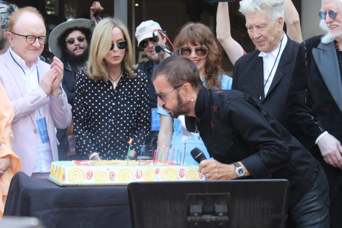 Ringo blows out the candles as (L-R) Peter Asher, Don Was, Barbara Bach, Jim Keltner, Jenny Lewis, David Lynch, and Edgar Winter look on