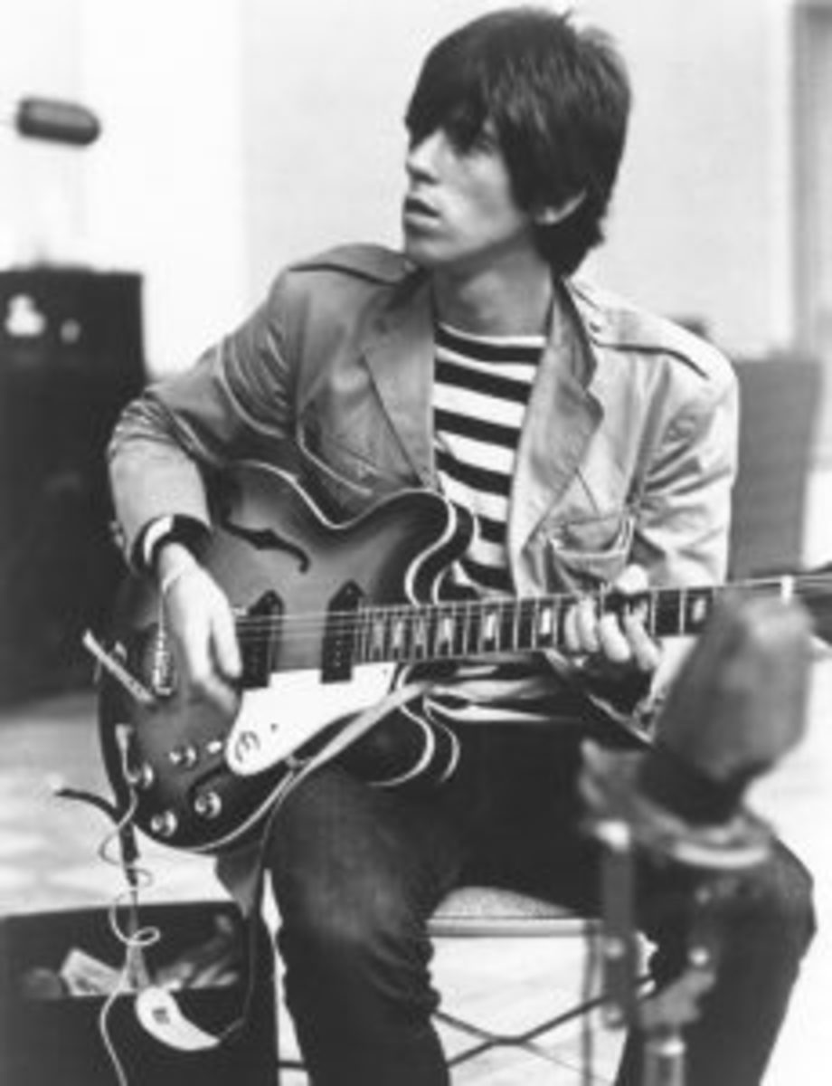Guitarist Keith Richards of The Rolling Stones sits on a chair in a recording studio and strums his Epiphone guitar in 1966. (Photo by Michael Ochs Archives/Getty Images).
