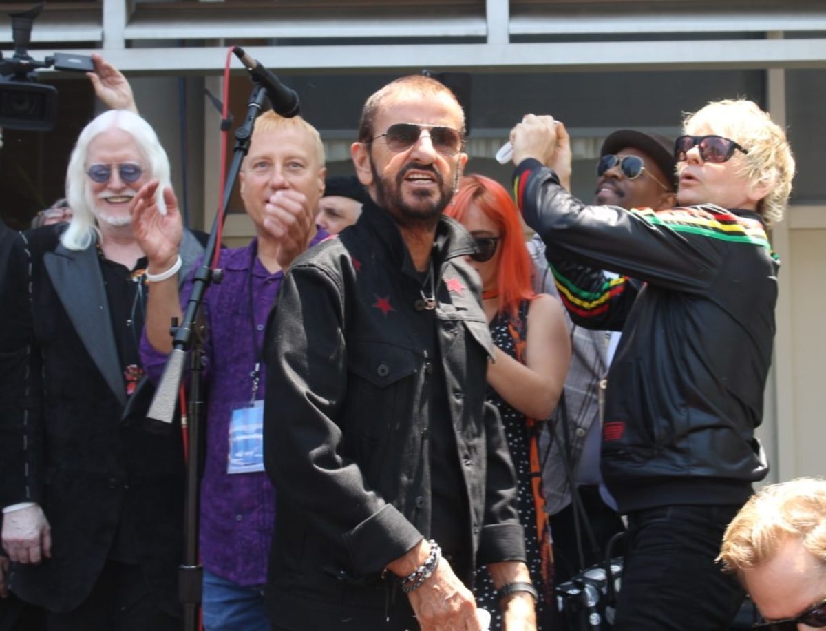 "Ringo and friends (including son Zak Starkey, far right) toss ""Peace & Love"" wristbands into the crowd"