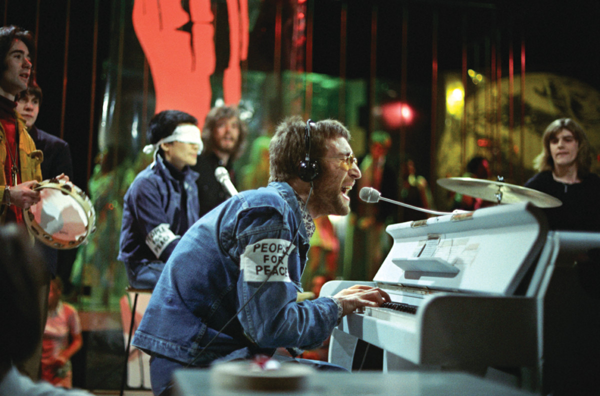 """John Lennon performing """"Instant Karma"""" on Top of the Pops, February 11, 1970, with Yoko Ono wearing a blindfold and bassist Klaus Voormann behind Ono. Photo byRon Howard/Redferns"""